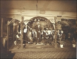 Eight member band preparing to play music at the Bismarck Cafe, Seattle, Washington, ca. 1904.