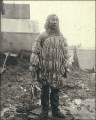 Eskimo man wearing gut parka and holding fish, Nome, Alaska, 1900.