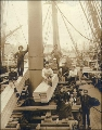 Men and one woman on the deck of an unidentified sailing vessel piled with stacks of lumber, Puget...