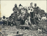 Eskimo men and boys posed with dead caribou in front of underground sod hut, Port Clarence,...