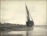 Sailing vessel SEQUOIA on the beach probably at low tide, Nome, Alaska, ca. 1900.