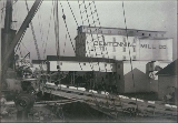 Conveyor belt loading goods onto ship at the Centennial Mill Co. dock, probably Tacoma,...