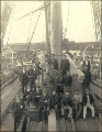 Crew seated on or standing next to piles of lumber on the deck of the three-masted ship KING...