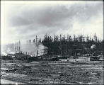 Port Blakely lumber mill showing sailing vessels at dock and log pond in foreground, Washington,...