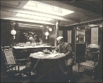 Crew member seated at a desk in one the interior cabins of the four-masted British bark GRENADA,...