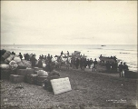 Groups of men with supplies on the beach preparing to depart for destinations on the mainland...
