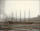 Five-masted schooner SNOW & BURGESS at anchor with log boom in foreground, Port Blakely,...