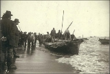 Eskimos unloading goods onto beach from umiak, or skin boat, Nome, Alaska, ca. 1900.