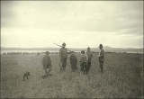 Eskimos in western clothing standing in a field, Port Clarence, Alaska, ca. 1900.