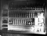 Liquor bottles in racks, interior of unidentified ship, Washington, ca. 1900