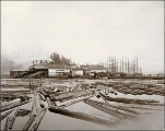 Port Blakely lumber mill showing log pond in foreground and sailing vessels at dock, Washington,...