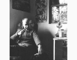 Kenneth Callahan seated in his studio, smoking a pipe, ca. 1965