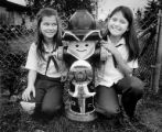 Fourth graders Brenda Fritts (at left) and Carolyn Langlot posing with a fire hydrant painted like...