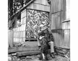 Kenneth Callahan seated outside his studio, with dog, ca. 1965