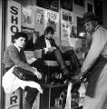 Musician Kelly Vance getting his shoes shined in front of Champion Display and Costume, 1928 Pike...