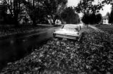 Seattle street and 1962 Cadillac Sedan Deville covered in wet leaves, Washington, April, 1976