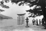 Itsukushima Torii with stone lantern, sightseers and water, Japan, 1961
