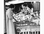 Merchant assisting customer at vegetable stall, Pike Place Market, Seattle, ca. 1965