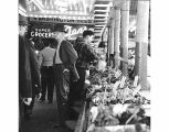 Visitors to the Pike Place Market beside vegetable stall, Seattle, ca. 1965