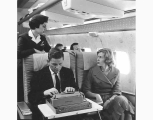Northwest Airlines aircraft interior showing man using typewriter, woman passenger and female...