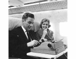 Northwest Airlines aircraft interior showing man using typewriter and woman passenger, ca. 1965,...