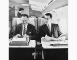 Two men on Northwest Airlines aircraft, one using typewriter, with female flight attendant in...
