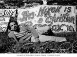 Bearded protester lies on the grass in front of hand painted protest signs, San Francisco,...