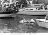 Man in inflatable boat surrounded by boats during the opening day of boating season, Seattle,...
