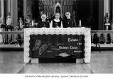 Nuns standing behind a banner in the chapel at Sacred Heart Villa (now Villa Academy), Seattle,...