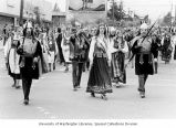 Parade participants, dressed in traditional bunads, celebrating Norway's independence day as they...