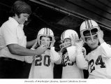 Coach Gary Sweeney helping (l to r) 12 year-olds Pat McCann, Jim Carroll, and Jeff Wade suit up at...