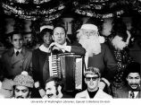 Man with accordian surrounded by mall employees and others during the Christmas ceremonies at...