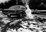 Melting snowman next to a Ford Mustang in a University of Washington parking lot, Seattle,...