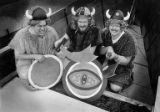 Three men dressed as vikings, brandishing scimitars and shields, pose in their Viking ship during...
