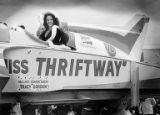 "Ballard Seafair Queen Tracy Gordon waving from aboard the hydroplane ""Miss Thriftway""..."