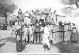 People gathered around public well with water containers, India, ca. 1921
