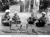 Four snake charmers and snakes, India, ca. 1921