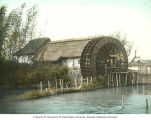 Building with water wheel next to stream, Japan, ca. 1921