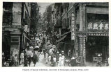 Crowded intersection with Queens Road showing pedestrians, shops and signs, Hong Kong, n.d.