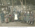 Group of children, with man and woman next to outdoor food vendor, Japan, ca. 1921