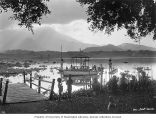 People on lakeshore with bamboo instruments called angklung, and boats on lake, near Garut, ca....