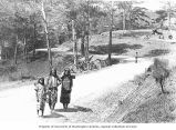 Three girls on road with baskets on their backs, Philippines, ca. 1921