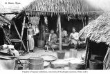 Village scene showing family in dwelling with cooking pots, Thailand, n.d.