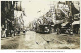 Nanking Road showing businesses, trolley, rickshaws, and pedestrians, Shanghai, China, ca. 1925