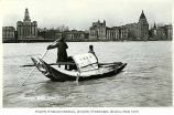 Sampan with city waterfront in background, Shanghai, China, ca. 1925