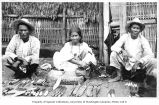 Men and woman selling knives in outdoor shop, Philippines, ca. 1913