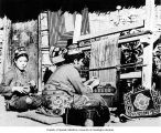 Seated Sherdukpen woman weaving rug on vertical loom and girl winding yarn, Dirang Dzong village, ...