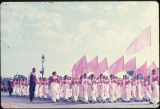 Group of girls walking in formation, wearing cranberry, pink, and white salwar kameez, during the...