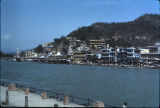Haridwar buildings, including a tall single-domed tower, viewed from across Ganges River,...