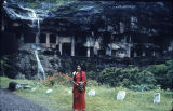 Mrs. I. Gairola standing in front of Buddhist rock-cut temples, Ellora, Maharashtra, India, ca....